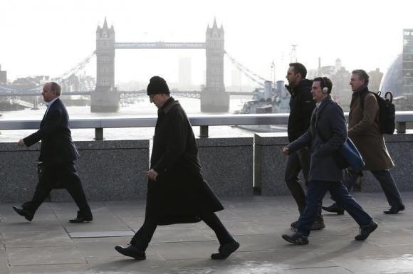 Tower Bridge is seen behind commuters as they walk across London Bridge during an Underground strike in London