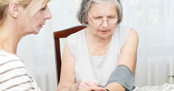 adult-daughter-checking-blood-pressure-of-elderly-mother_573x300